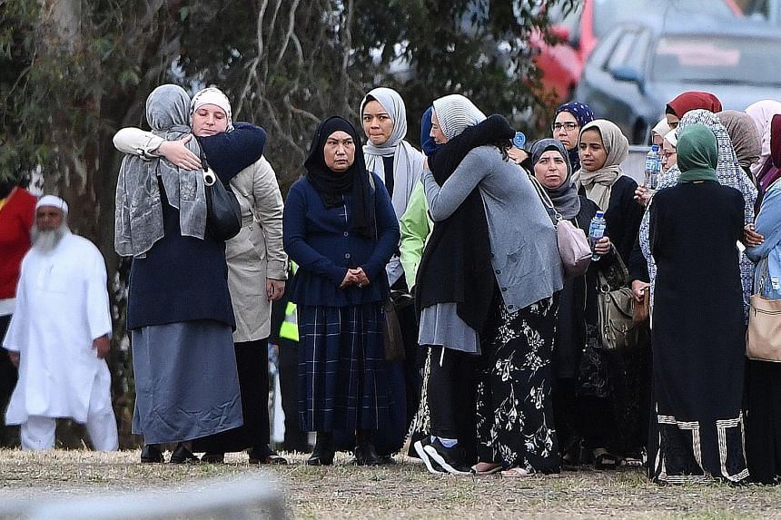 Mourners consoling one another at the funeral of 14-year-old Sayyad Ahmed Milne, one of the 50 people killed in last Friday's attacks on two mosques, at the Memorial Park Cemetery in Christchurch yesterday.