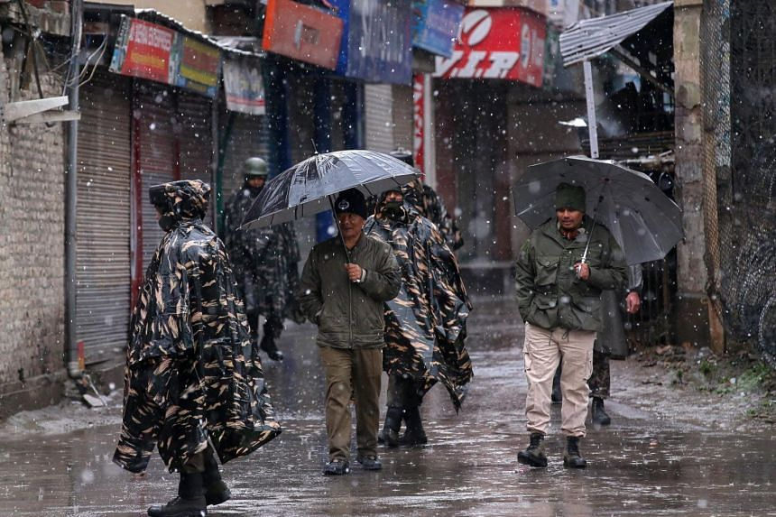 India's Central Reserve Police Force (CRPF) personnel patrol a street as it snows in Srinagar, Kashmir, on March 20, 2019.