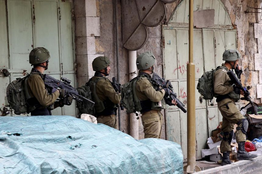 Armed Israeli soldiers patrol the streets during clashes between Palestinians and Israeli troops in the West Bank city of Hebron, on March 15, 2019.