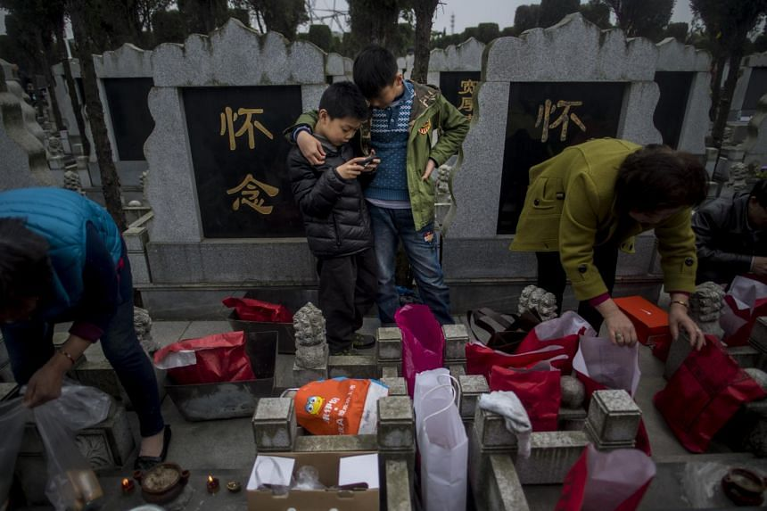 Children playing on a smartphone while their family pay respects to their ancestors at a public cemetery in Shanghai, on April 4, 2017.