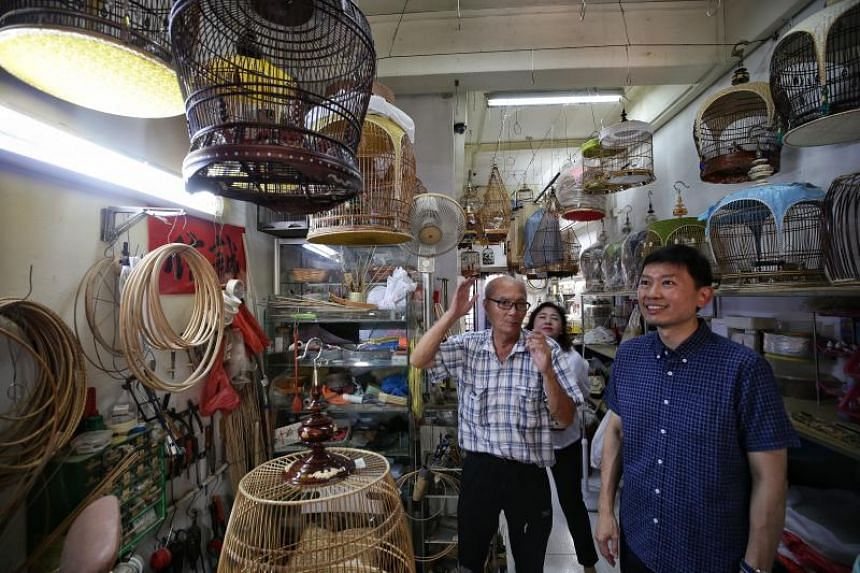Senior Minister of State for Trade and Industry Chee Hong Tat (right), accompanied by tourist guide Catherine Ross (centre), visiting bird-cage maker and principal consultant of BirdsAsia Teng Leng Foo during a tour of the Ang Mo Kio precinct on Marc