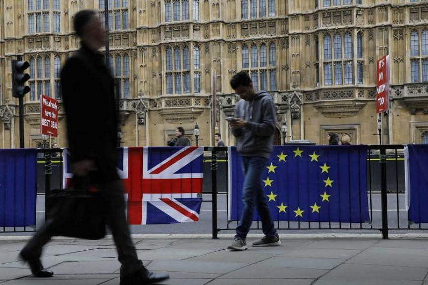 Pedestrians walking past a British national flag (left) and an EU flag outside the Houses of Parliament in central London.