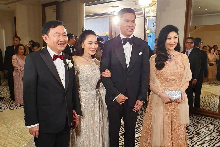 Former Thai prime ministers Thaksin Shinawatra (left) and his sister Yingluck (right) posing with the bride Paetongtarn Shinawatra and her groom Pidok Sooksawas.