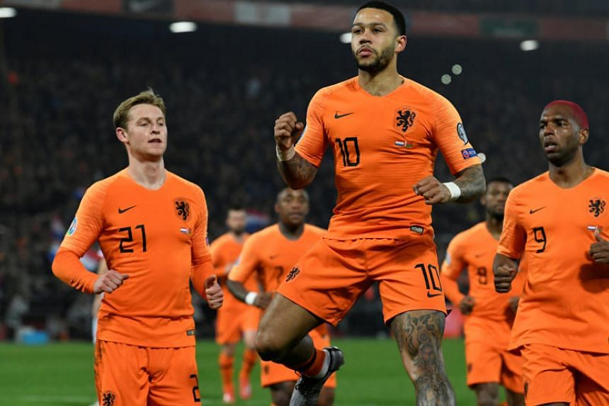 The Netherlands' Memphis Depay celebrates scoring their third goal during their opening Euro 2020 qualifier against Belarus in Rotterdam on March 21, 2019.
