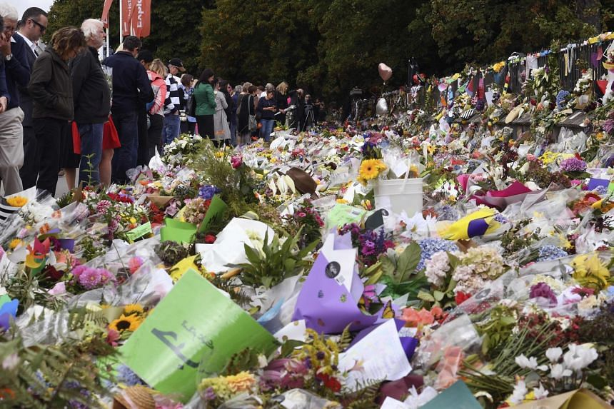People paying tribute at the Botanic Gardens in Christchurch on March 21, after the twin mosque shooting massacre that claimed the lives of fifty people.