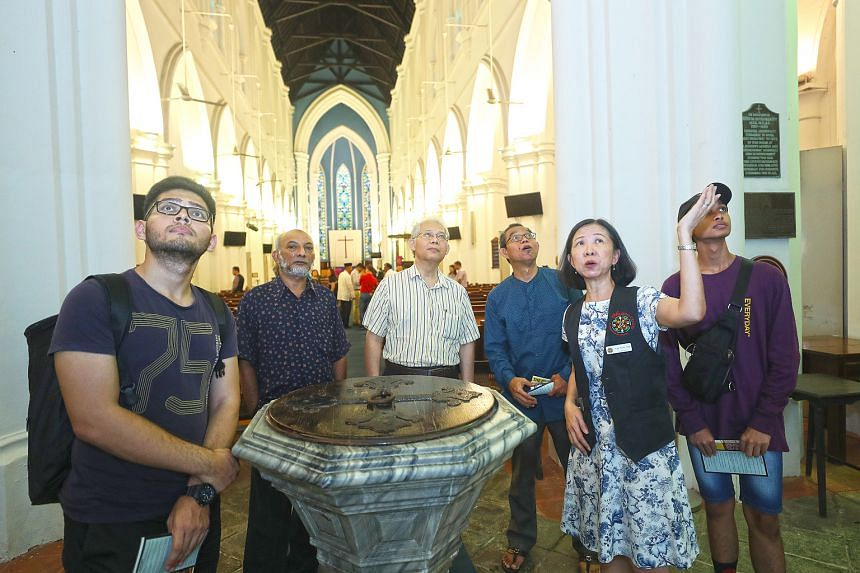 Ms Yap Soik Yee, a volunteer docent with St Andrew's Cathedral, pointing out the national monument's rich heritage to members of the Woodlands Malay Activity Executive Committee as well as mosque and temple leaders during their visit yesterday.