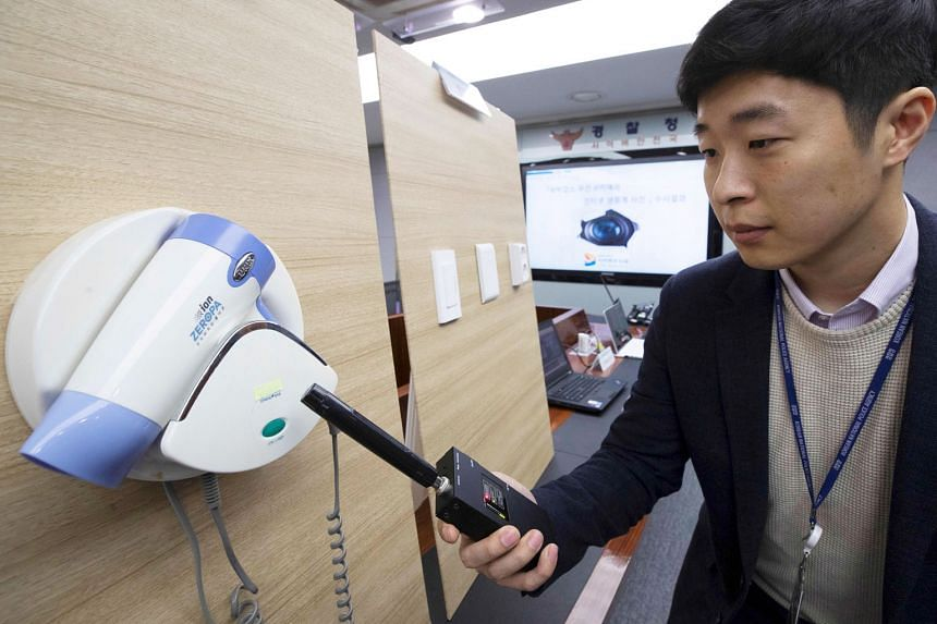A police officer holding up a detector in front of a hidden camera installed in a hairdryer holder. In the live-streaming case, tiny cameras were planted in 42 rooms in 30 motels, hidden in places such as wall sockets and digital TV boxes.