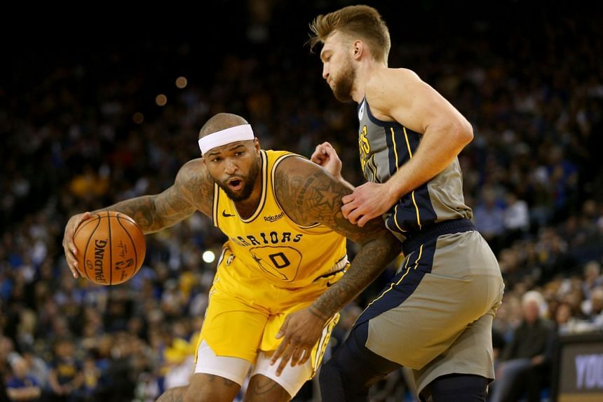 Golden State Warriors center DeMarcus Cousins (in yellow) attempts to drive past Indiana Pacers forward Domantas Sabonis in the fourth quarter at Oracle Arena.