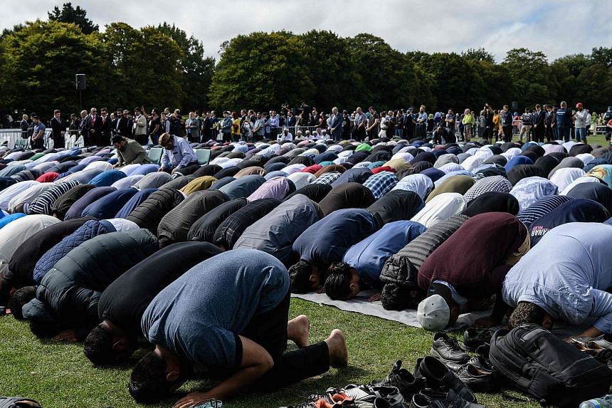 Above: Muslim men praying in a park near the Al Noor Mosque in Christchurch, shortly after two minutes of silence was observed yesterday in memory of the victims. Left: A police officer outside the Kilbirnie Mosque in Wellington. New Zealand has been