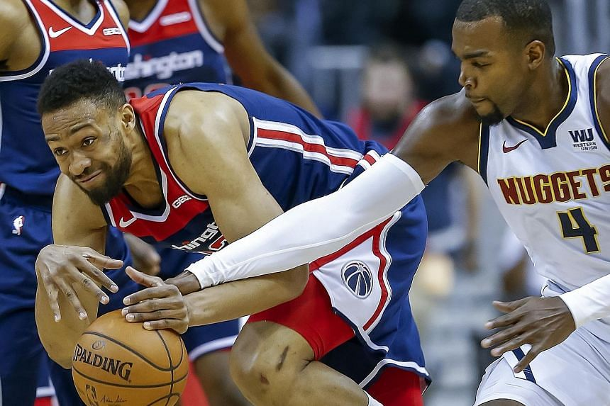 Denver Nuggets forward Paul Millsap tussling with Washington Wizards forward Jabari Parker for the ball at the Capital One Arena on Thursday. The Nuggets won the National Basketball Association game 113-108 with eight players scoring double figures.
