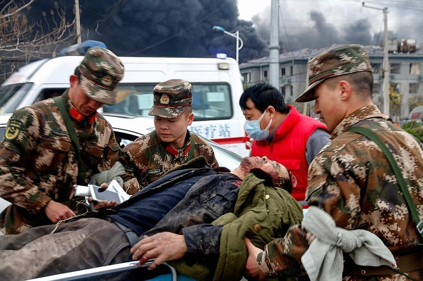 Above: Firefighters at work early yesterday, following the chemical blast in Jiangsu on Thursday afternoon. Below: An injured man being taken away from the scene of the explosion on Thursday. Damaged buildings in the wake of a blast on Thursday at a