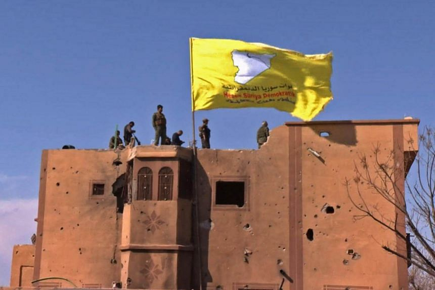 US-backed Syrian Democratic Forces raising their flag atop a building in the Islamic State's last bastion in the eastern Syrian village of Baghuz, on March 23, 2019.