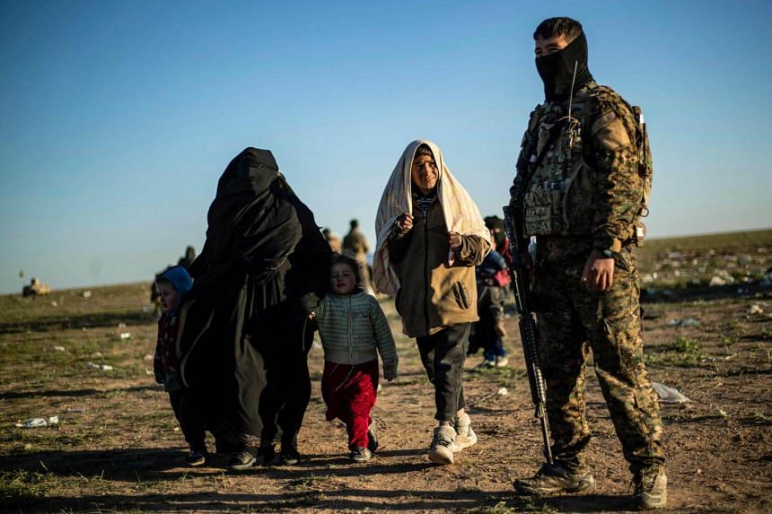 A member of the Kurdish-led Syrian Democratic Forces stands by as people walk after leaving the Islamic State's last holdout of Baghouz, on March 1, 2019.