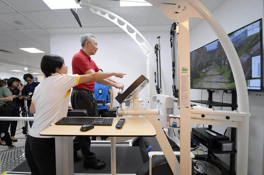 Prime Minister Lee Hsien Loong, assisted by Senior Physiotherapist Ma Shi Min, tries out a high-tech treadmill at Sengkang General Hospital, on March 23, 2019.