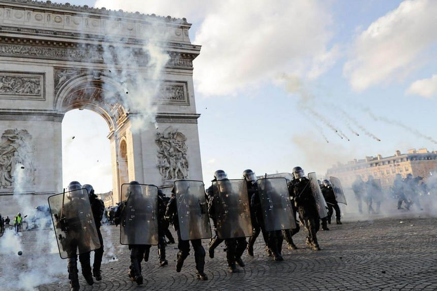 Riot police charge using tear gas canister at the Arc de Triomphe on the Place de l'Etoile in Paris, on March 16, 2019.
