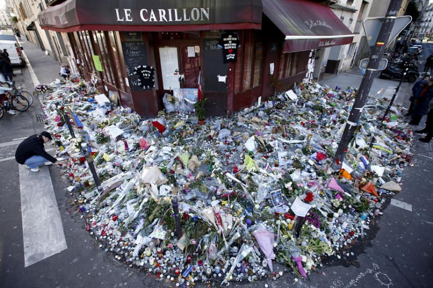People mourn outside Le Carillon restaurant a week after a series of deadly attacks in the French capital Paris, on Nov 22, 2015.