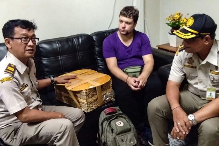 Indonesian officials with detained Russian national Andrei Zhestkov (centre), accused of smuggling a two-year-old orang utan in a rattan basket, at Bali's international airport in Denpasar on March 23, 2019.