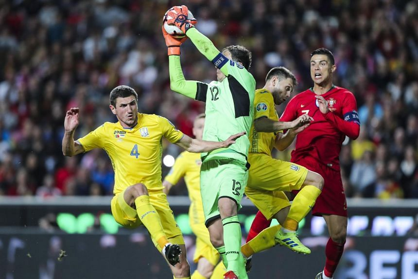Portugal's Cristiano Ronaldo (right) fights for the ball with Ukraine's Sergii Kryvstov (left), goalkeeper Andriy Pyatov and Oleksandr Karavaev (second from right) during the Uefa Euro 2020 qualification match between Portugal and Ukraine at Luz Stad