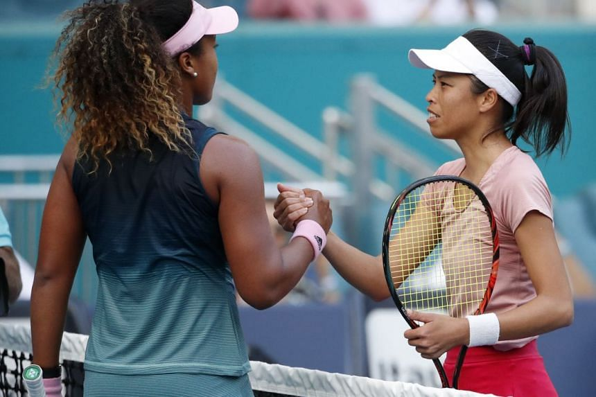 Hsieh Su-wei of Chinese Taipei with Naomi Osaka of Japan at the net after defeating her in the Miami Open tennis tournament on March 23, 2019.