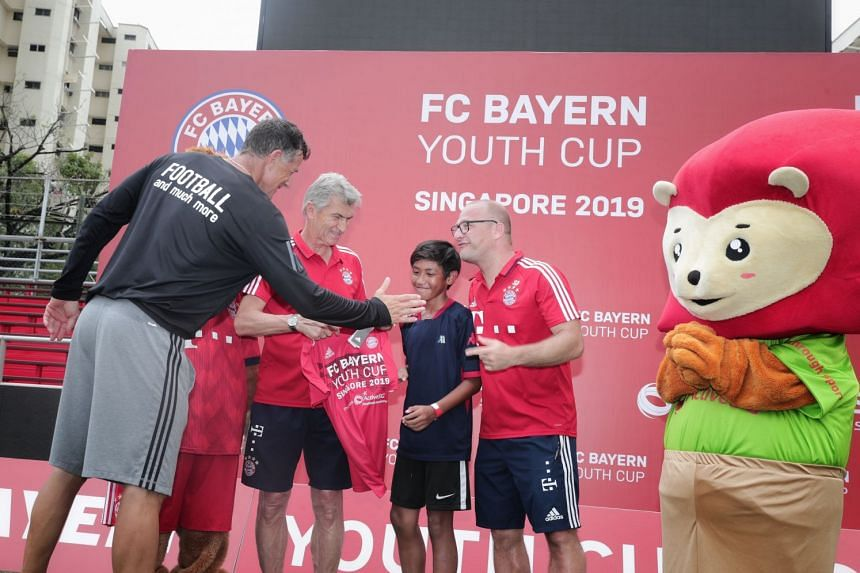 From left: Aleksandar Duric, principal of the ActiveSG football academy, Germany's 1990 World Cup winner Klaus Augenthaler and Sebastian Dremmel, head coach of Bayern's international programme, with Nur Asis Ijilrali.