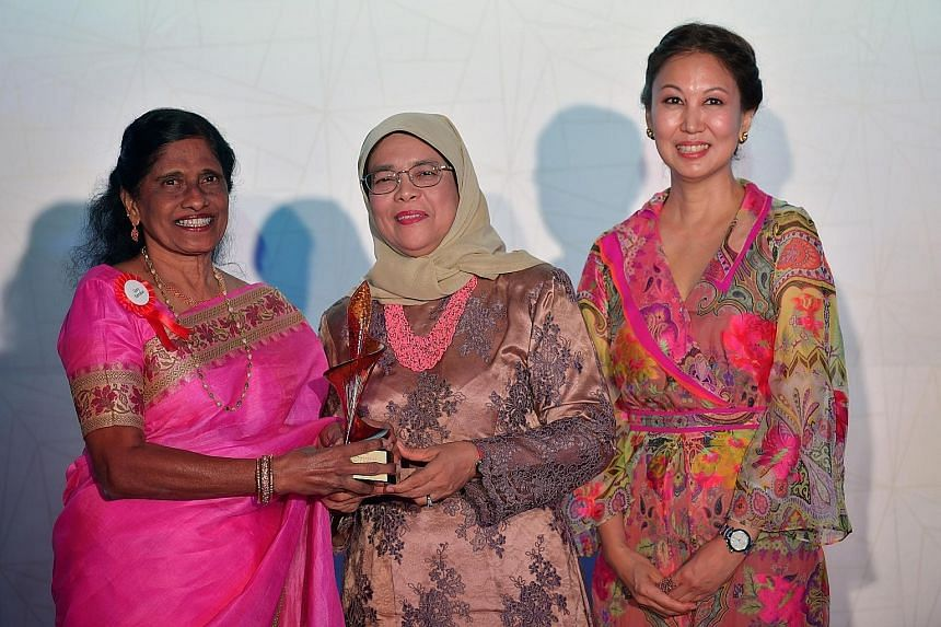 Mrs Glory Barnabas, one of eight new inductees into the Singapore Women's Hall of Fame, receiving her trophy from President Halimah Yacob during last night's ceremony. With them was SCWO president June Goh.
