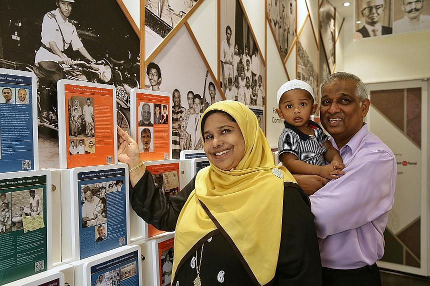 Madam Mumtaj Bivi, with her husband Naseer Ghani and their grandson Arfan Hassan Ghani Anwar, with old photos of her parents and ancestors from Tamil Nadu, India, at the Nagore Dargah Indian Muslim Heritage Centre in Telok Ayer. The free photo exhibi