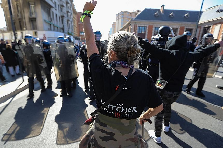 A demonstrator in Nice, France, gesturing at riot police officers during the 19th consecutive weekend of protests against President Emmanuel Macron's government yesterday.