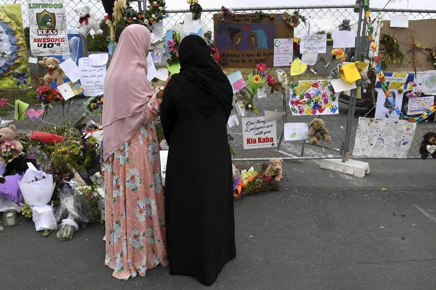 Two people look at tributes left at the Linwood Islamic Centre which remains closed despite the reopening of city's Al Noor mosque, in Christchurch, on March 23, 2019.