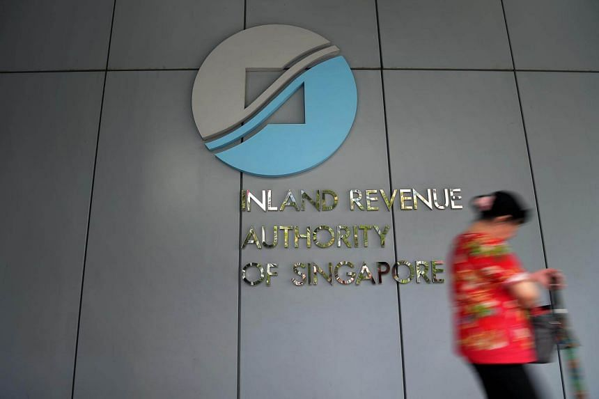 A lady walks past the Inland Revenue Authority of Singapore logo at IRAS building along Newton Road.
