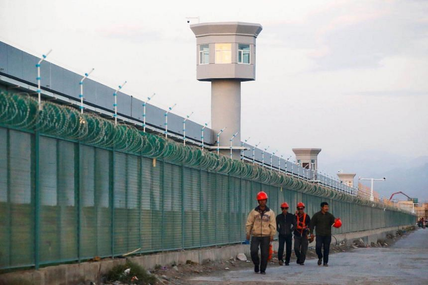 Workers walk by the perimeter fence of what is officially known as a vocational skills education centre in Dabancheng in Xinjiang Uighur Autonomous Region, China, on Sept 4, 2018.