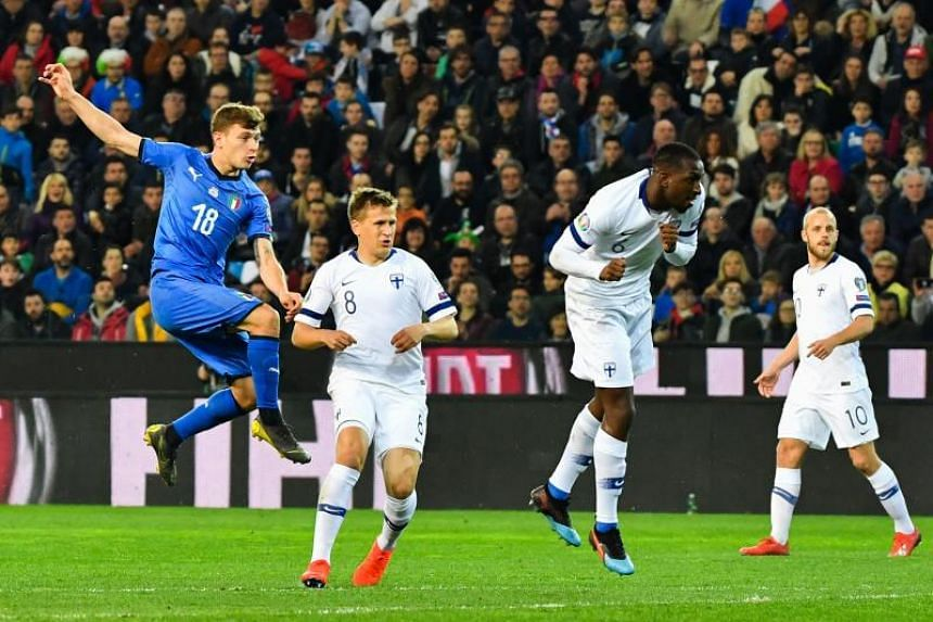 Italy's midfielder Nicolo Barella (L) shoots to open the scoring during the Euro 2020 Group J qualifying football match between Italy and Finland on March 23, 2019 at the Friuli stadium in Udine.