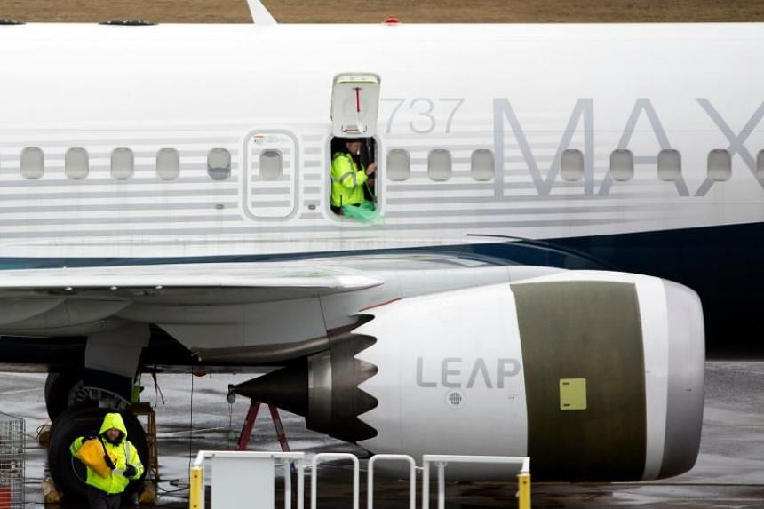 Workers are pictured next to a Boeing 737 Max 9 airplane on the tarmac at the Boeing Renton Factory in Renton, Washington.