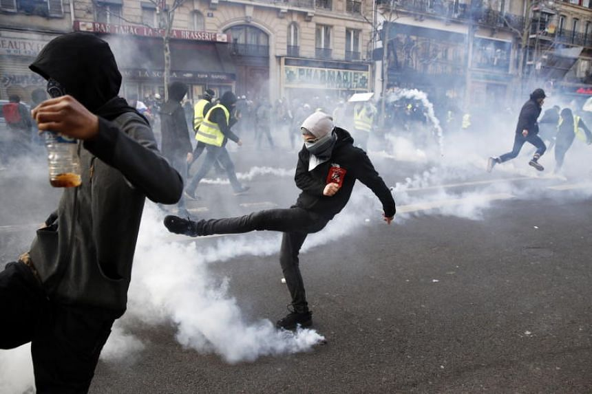 "Protesters from the ""Yellow Vests"" movement clash with French anti-riot police near Montmartre during the 'Act XIX' demonstration in Paris, France, on March 23, 2019."