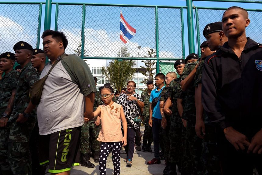 Civilians walk by as soldiers line up to vote in the general election at a polling station in Bangkok on March 24, 2019.