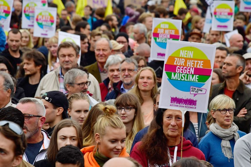 """Placards at a rally in Germany last year said """"No to hatred against Muslims"""". A study shows the number of attacks against Muslims has fallen there but there is """"Islamophobia without Muslims"""" in Eastern Europe."""