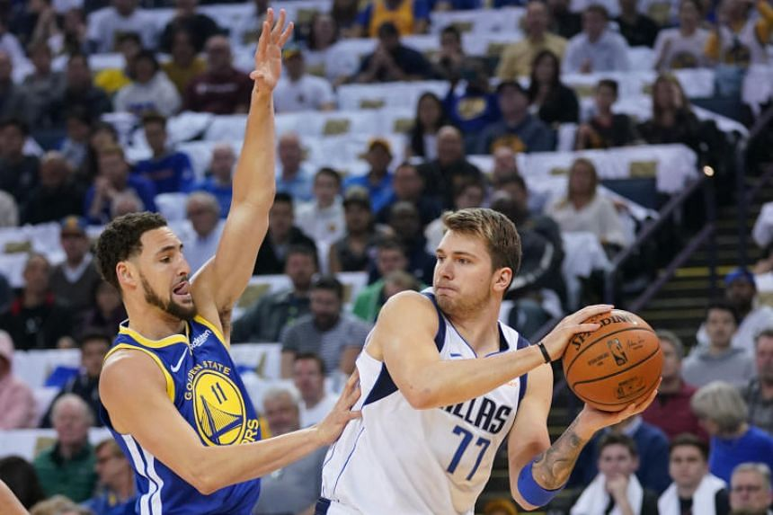 Dallas Mavericks forward Luka Doncic (right) looking to pass the ball against Golden State Warriors guard Klay Thompson during their NBA match on March 23, 2019.