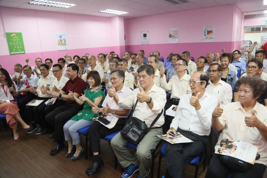 Dr Amy Khor, Senior Minister of State for Health (centre) and Mr Ang Wei Neng, chief executive of ComfortDelGro Taxi (in red) with a group of ComfortDelGro cab drivers at a sharing session by the Silver Generation Ambassadors on the Merdeka Package o