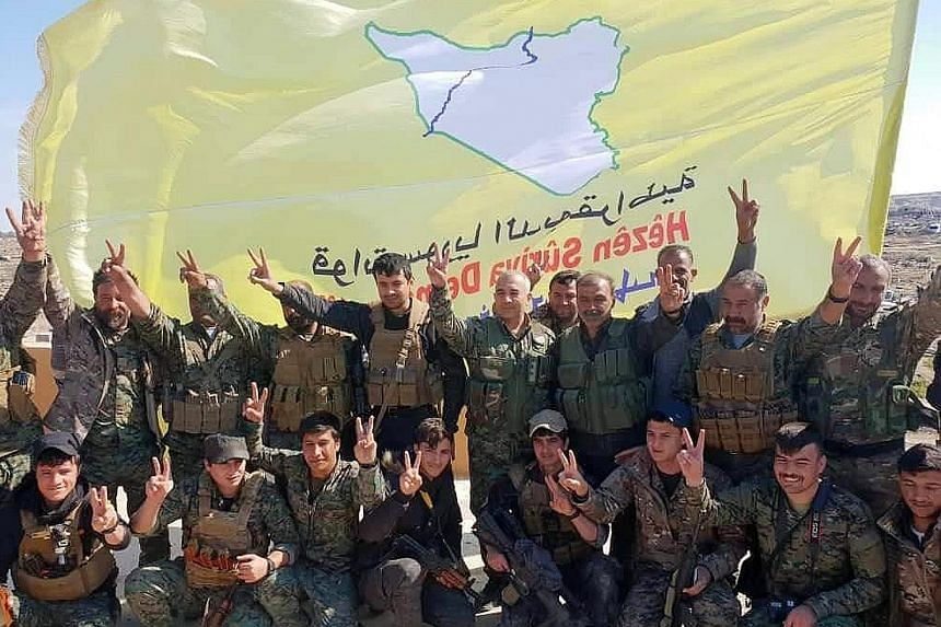 Fighters of the US-backed Syrian Democratic Forces celebrating on Saturday their victory over ISIS in the village of Baghuz in Syria, where the Islamist militants made their last stand. US President Donald Trump with maps of Syria and Iraq showing th