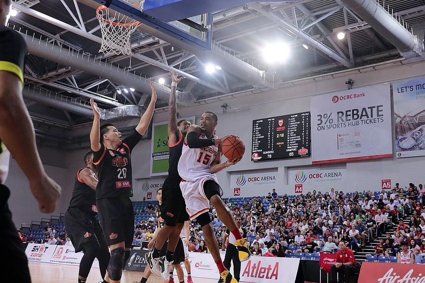 Mono Vampire players trying to prevent Singapore Slingers' Xavier Alexander from scoring at the OCBC Arena yesterday, but he scored 26 points to become the ABL's all-time leading scorer with 2,062 points.