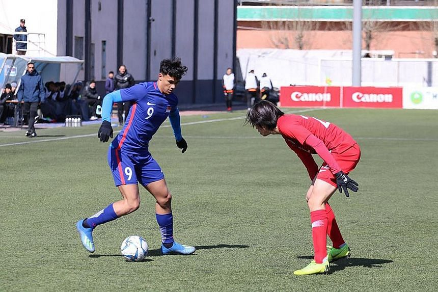 Singapore's Ikhsan Fandi (in blue), seen here in an earlier match against Hong Kong, scored a superb solo goal within a minute of kick-off against North Korea yesterday.