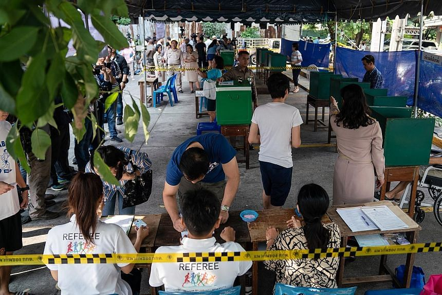 Left: Voters checking in at a polling station in Bangkok yesterday. Around 51 million Thais were eligible to vote, casting a single ballot for their preferred constituency candidates. Right: Voters casting their ballots in Bangkok's Thawiwit School y