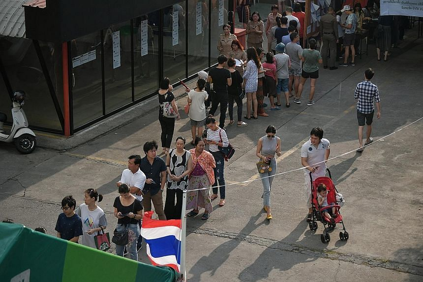 Voters at a polling station in a local car service centre in the Huay Kwang district of Bangkok yesterday. Millions of Thais braved long queues and blistering heat to vote in the long-awaited elections. An election official presenting a ballot for in