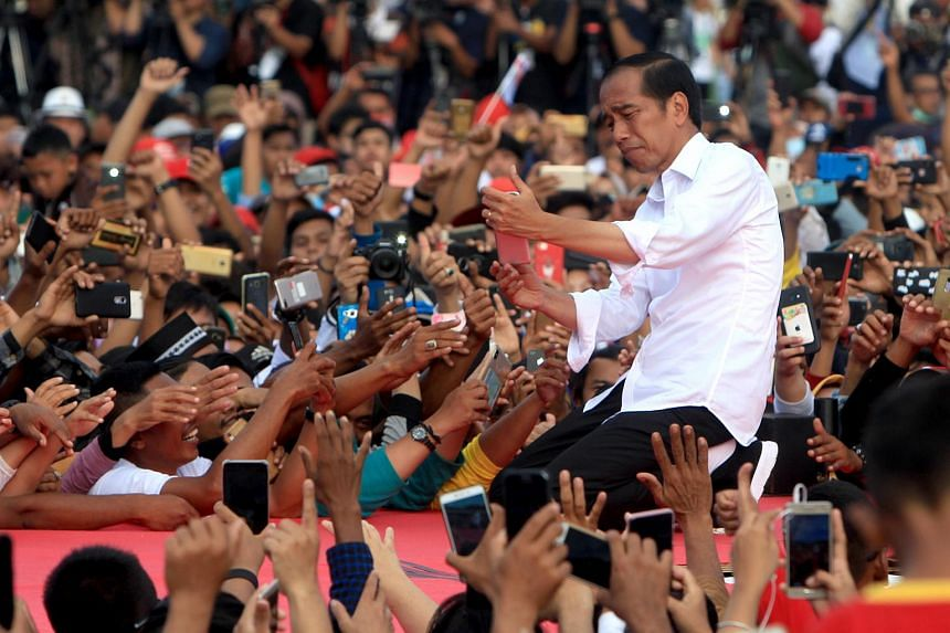 Indonesian incumbent president from the Indonesian Democratic Party of Struggle Joko Widodo (centre) takes a selfie with his supporters during his first day of campaign rallying in Serang, Indonesia, on March 24, 2019.