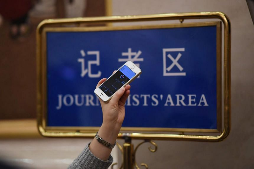 A journalist holding up a mobile phone to record a speech in the Great Hall of the People during the National People's Congress in Beijing on March 7, 2019.