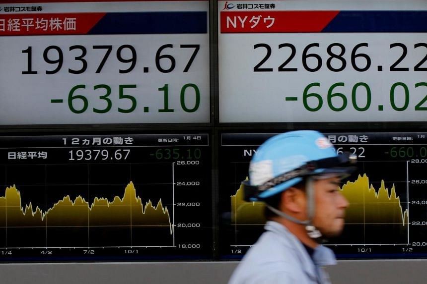 A man walks past electronic boards showing the Nikkei average and the Dow Jones Industrial Average outside a brokerage in Tokyo.