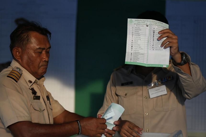 An election commission official displays a ballot paper while counting votes during the 2019 Thai general election on March 24, 2019.