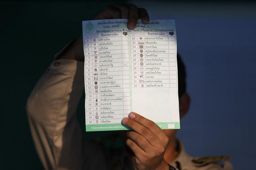 An election commission official displays a ballot paper to the media while counting votes during the 2019 Thai general election.