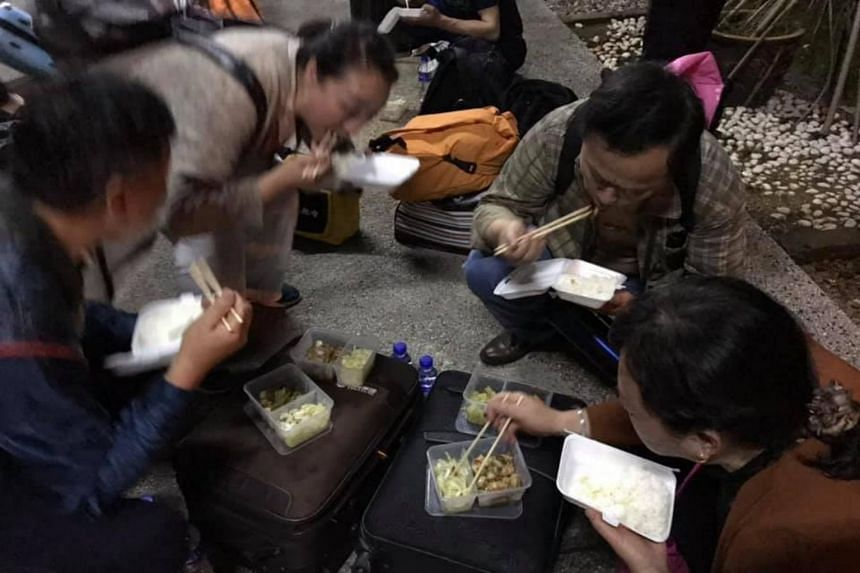 Tourists eating a packed food dinner by the side of the road after purportedly having to wait for seven hours to clear Malaysian Customs.