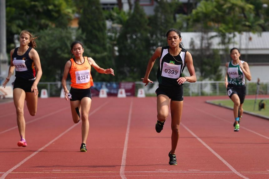 Raffles Institution's Grace Shani Anthony (second from right) crossing the finish line to win the Schools National A Division girls' 200m final ahead of (from left) Anglo-Chinese School (International)'s Camille Alix Damas, Singapore Sports School's
