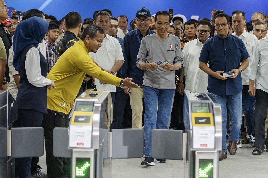 Indonesian President Joko Widodo (centre) and Jakarta Governor Anies Baswedan (right) at the Istora-Mandiri station, at the inauguration of Jakarta's first mass rapid transit line yesterday.